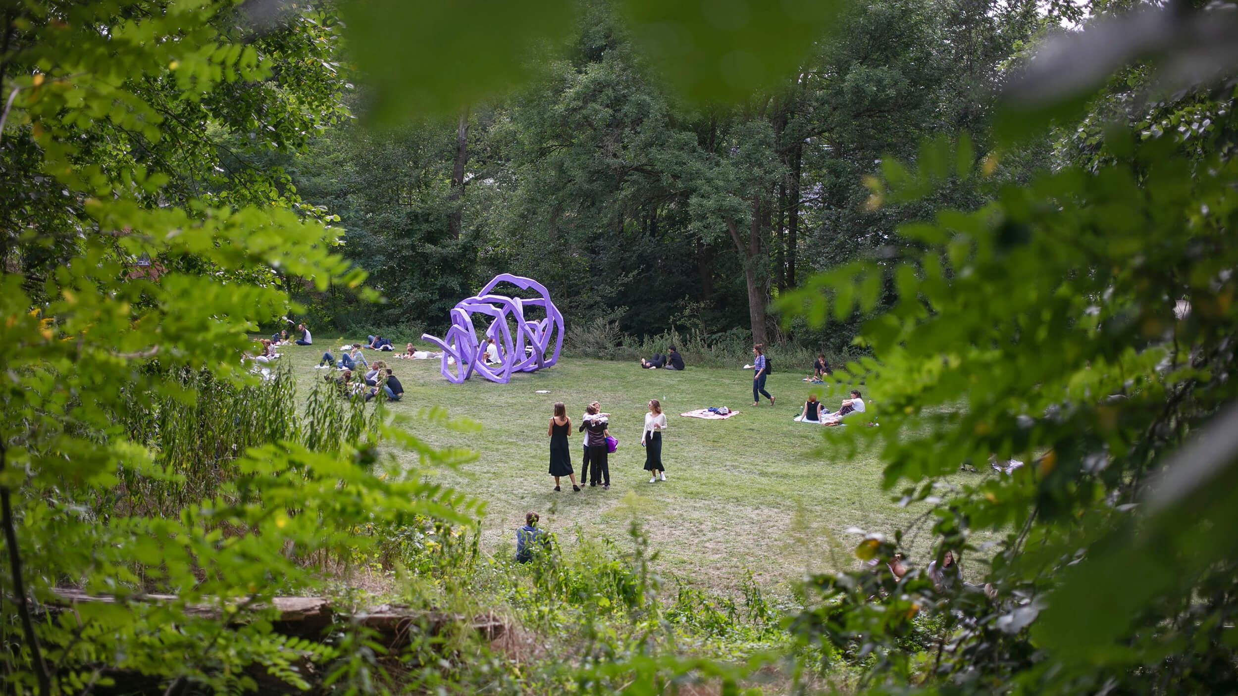 Foto von der Art Biesenthal 2019. Zu sehen ist eine lila Skulptur auf einer Wiese, drumherum Menschen.