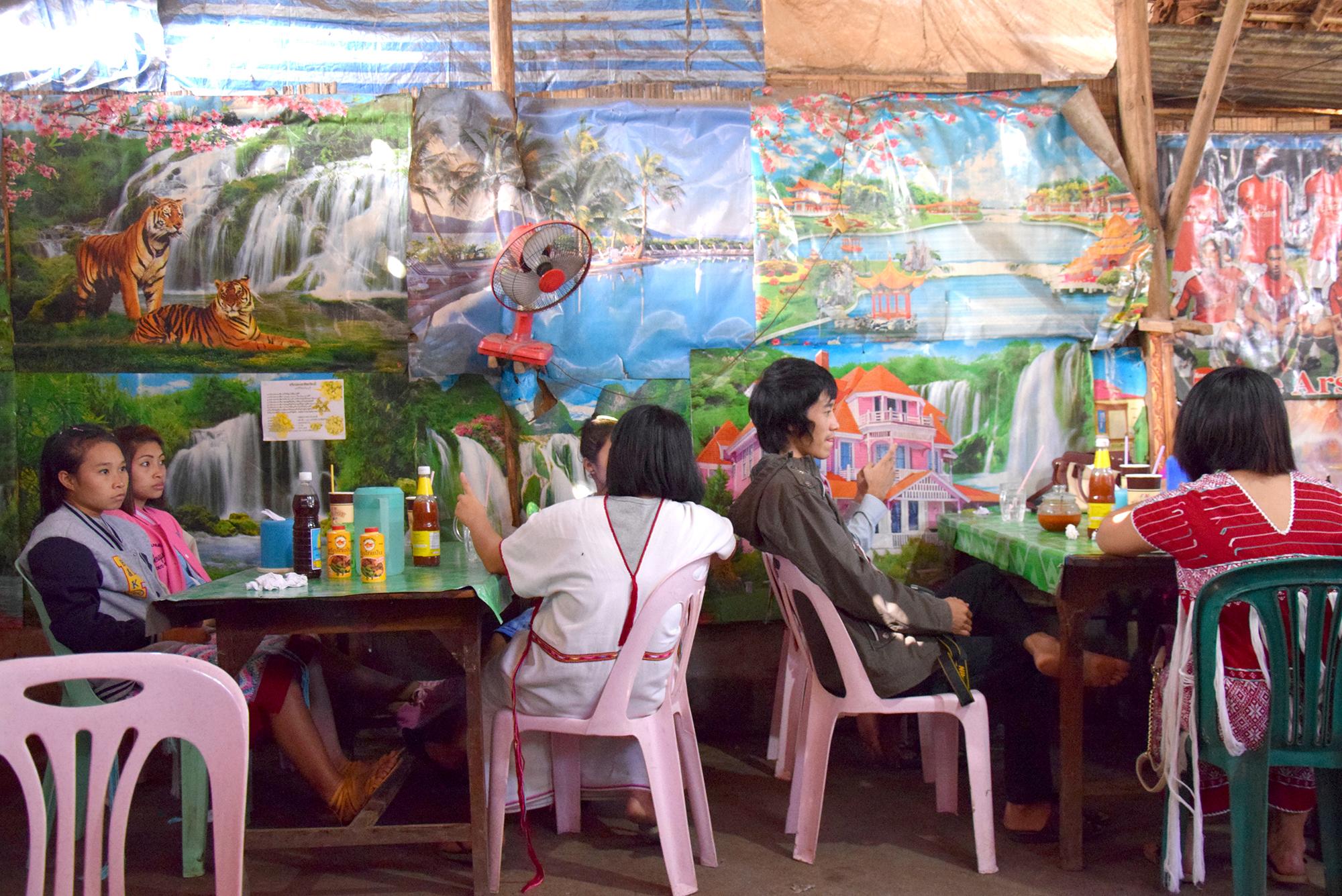 Menschen sitzen vor bunter Kulisse auf rosafarbenen Plastikstühlen. Still aus einer Videoarbeit von Belle Phromchanya.