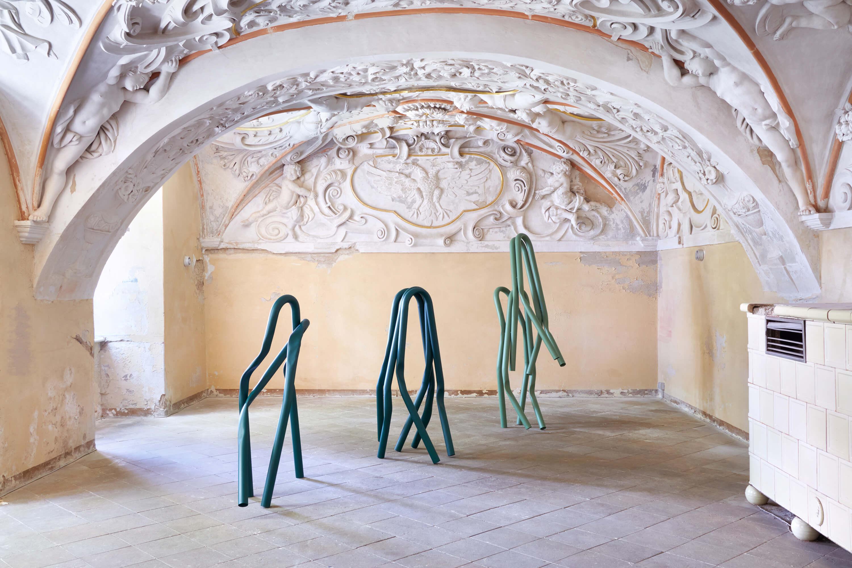 Lichtdurchfluteter Innenraum des Schloss Lieberose. Zu sehen sind drei Metallskulpturen in Grüntönen von Bettina Pousstchi.