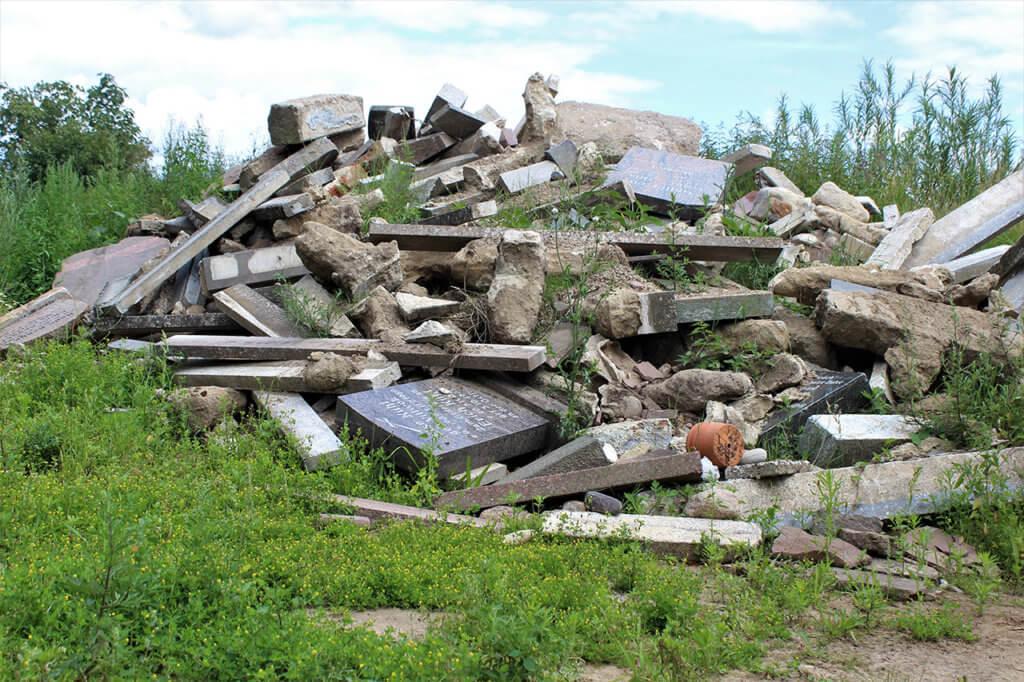 Fotografie eines von Unkraut bewucherten Schutthaufens mit verschiedenen Steinen. Erst auf den zweiten Blick fällt auf, dass es sich um Grabsteine handelt.