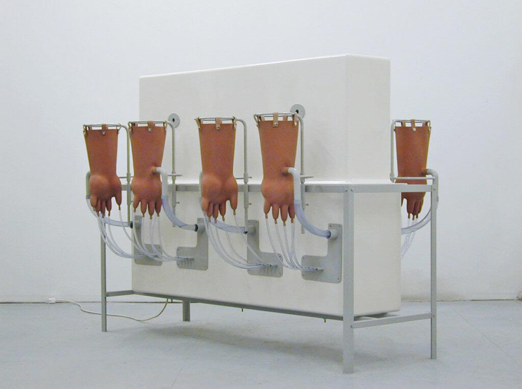 Installation ANGORA von Gunter Unterbuttre. Weiße Maschine mit vier Händen.