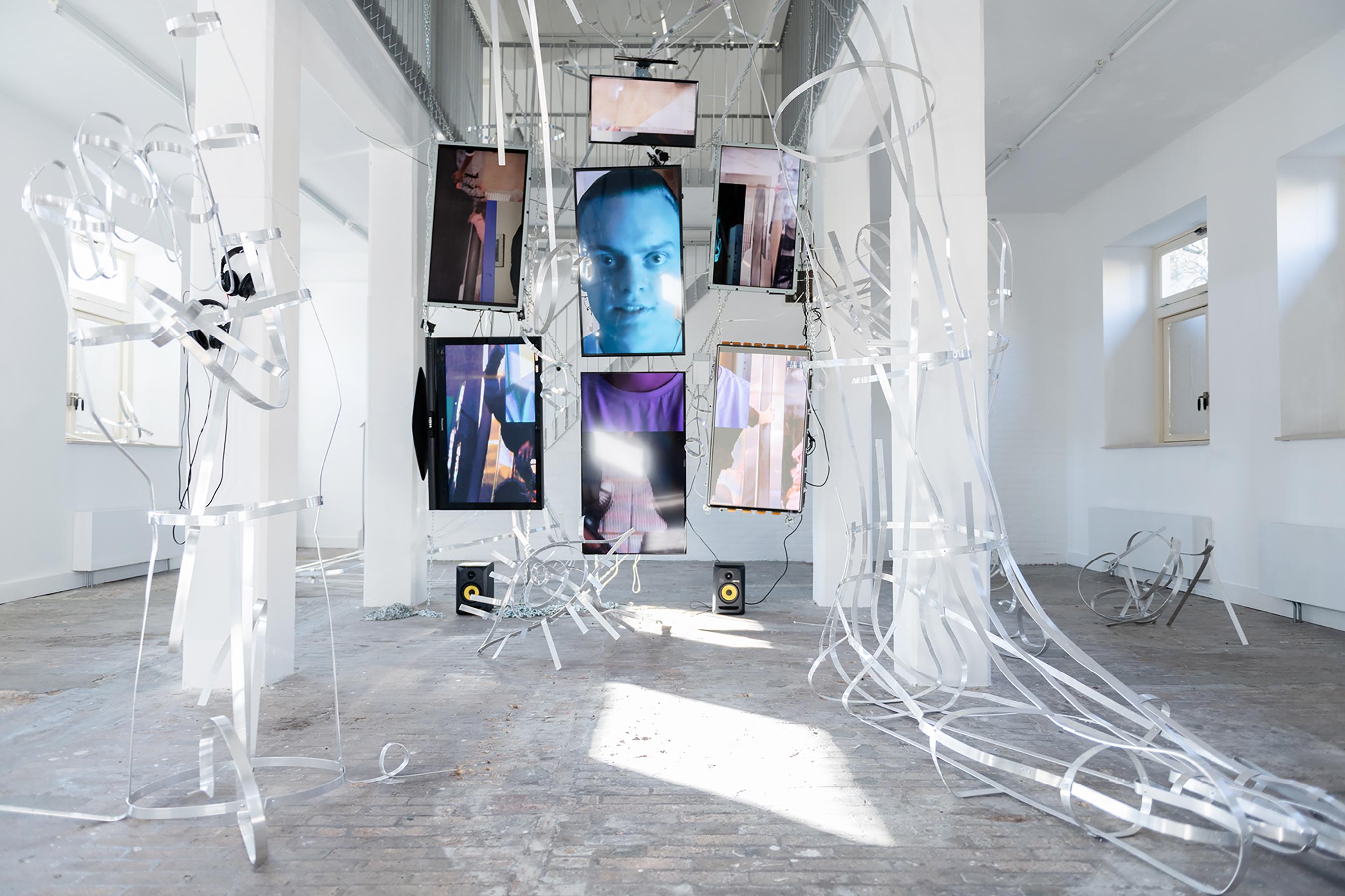 Installation von Johannes Büttner mit von der Decke hängenden Screens.