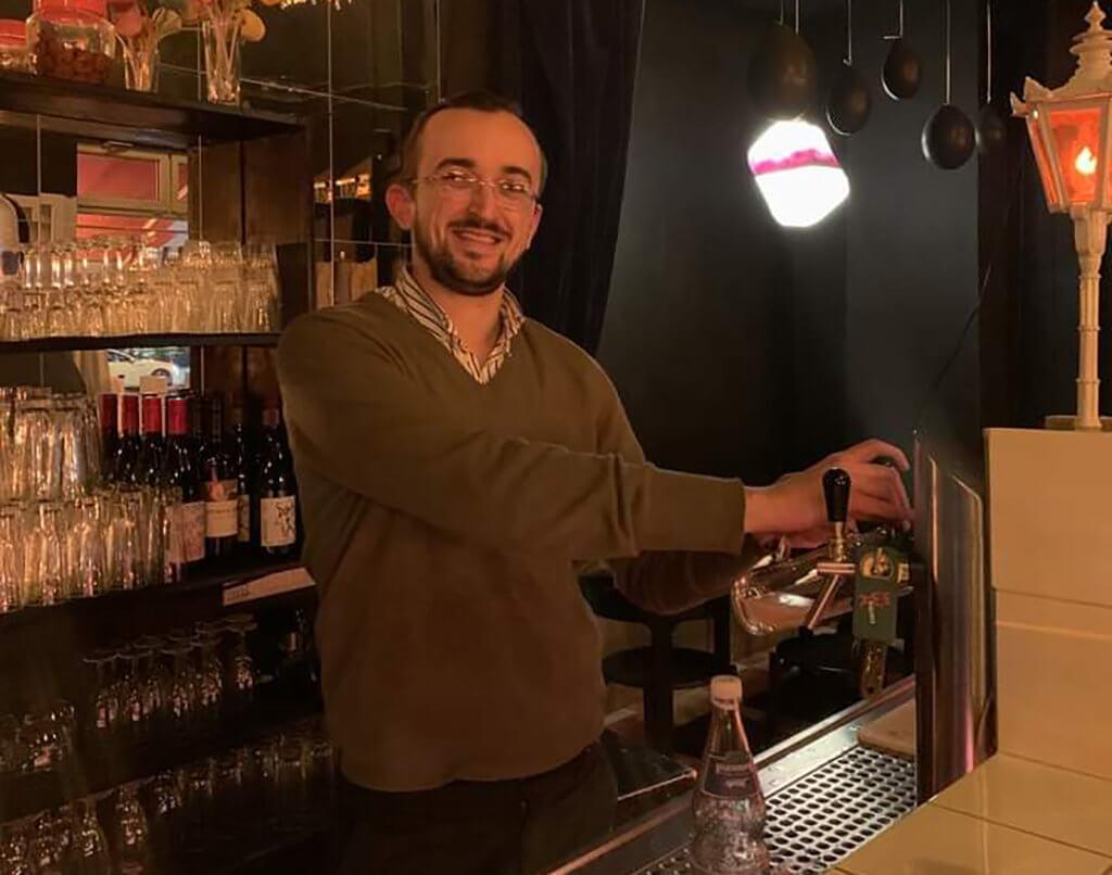 Zu sehen ist der Künstler Josip Novosel hinter dem Tresen der TV Bar in Berlin. Er zapft gerade ein Bier.