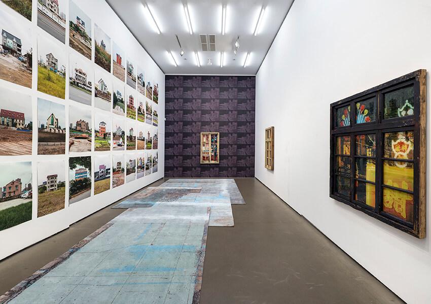 Blick in einen White Cube mit Fotografien zur linken Seite und einer lilafarbenen Wand mittig