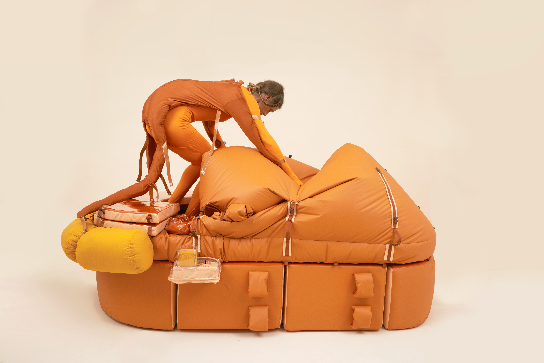 """Lucy McRae steigt in ihre Arbeit """"Solitary Survival Raft"""", eine Art orangefarbenes Rettungsboot."""