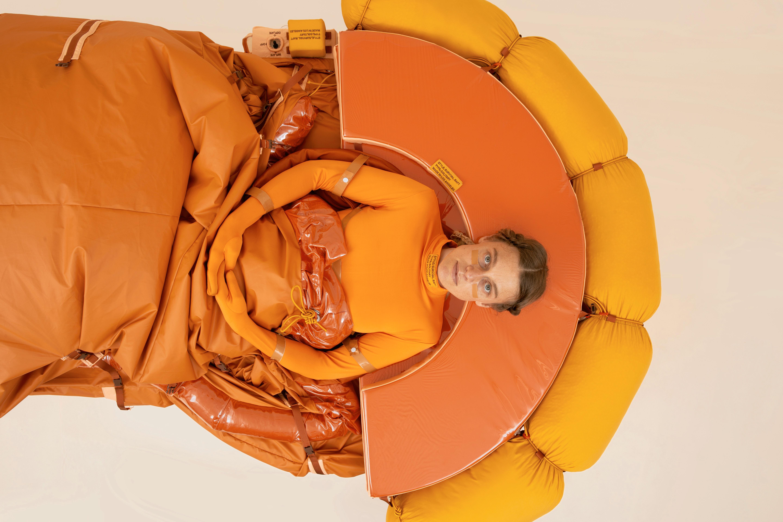 """Lucy McRae liegt in ihrer Arbeit """"Solitary Survival Raft"""", eine Art orangefarbenes Rettungsboot."""