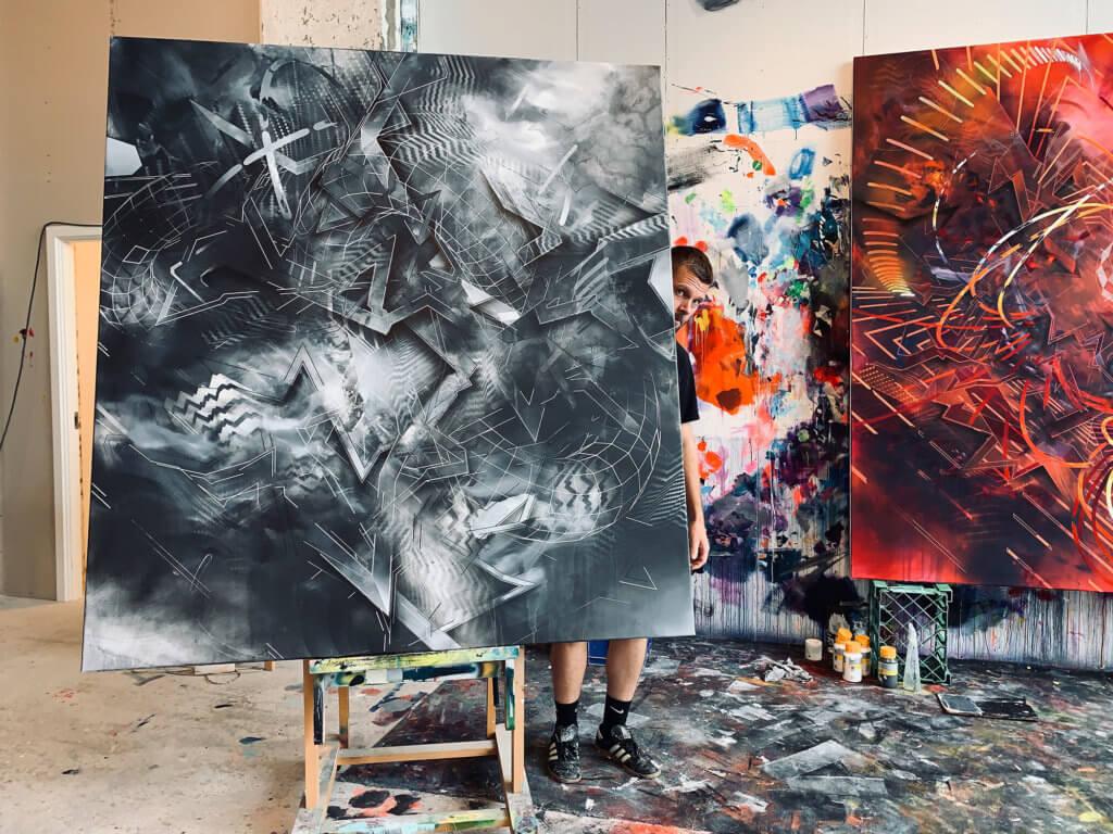 Der Künstler Morten Andersen präsentiert ein großes Werk mit abstrakten Grafitti-Elementen in Schwarz-Weiß