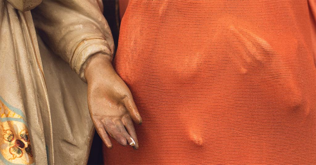 Die Hand einer Holzpuppe vor orangenem Stoff