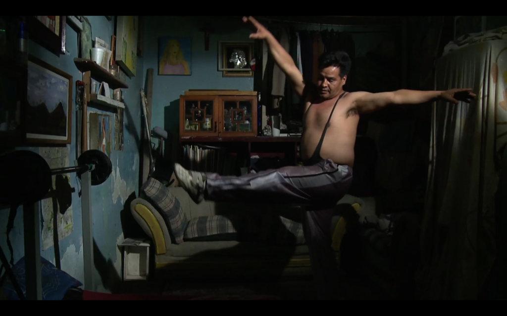 Zu sehen ist ein Videostill von Sarah Minter, abgebildet ist ein Mann der tanzt, sein Öberkörper ist nackt.