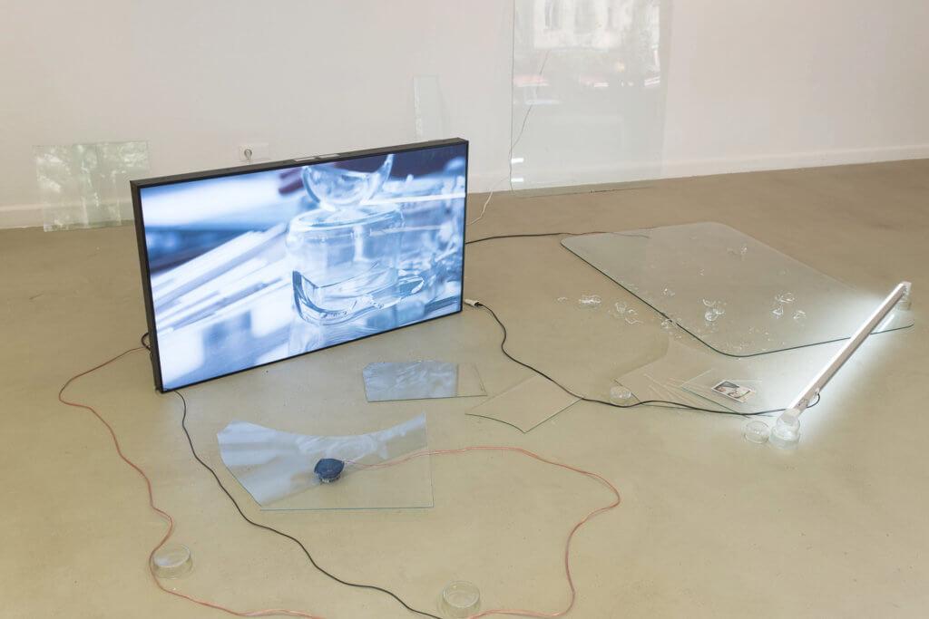 Ein Bildschirm, der auf einem Boden steht, umgeben von Scherben.