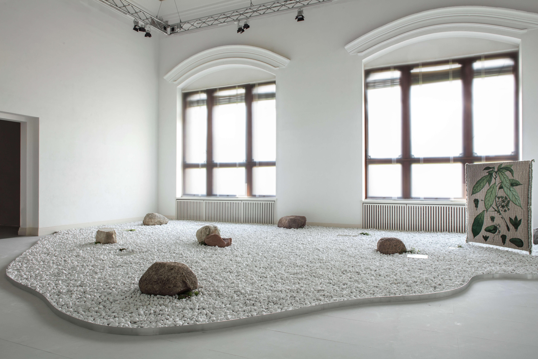 Weißer Raum mit zwei Fenstern und einem Becken aus weißen Steinen.