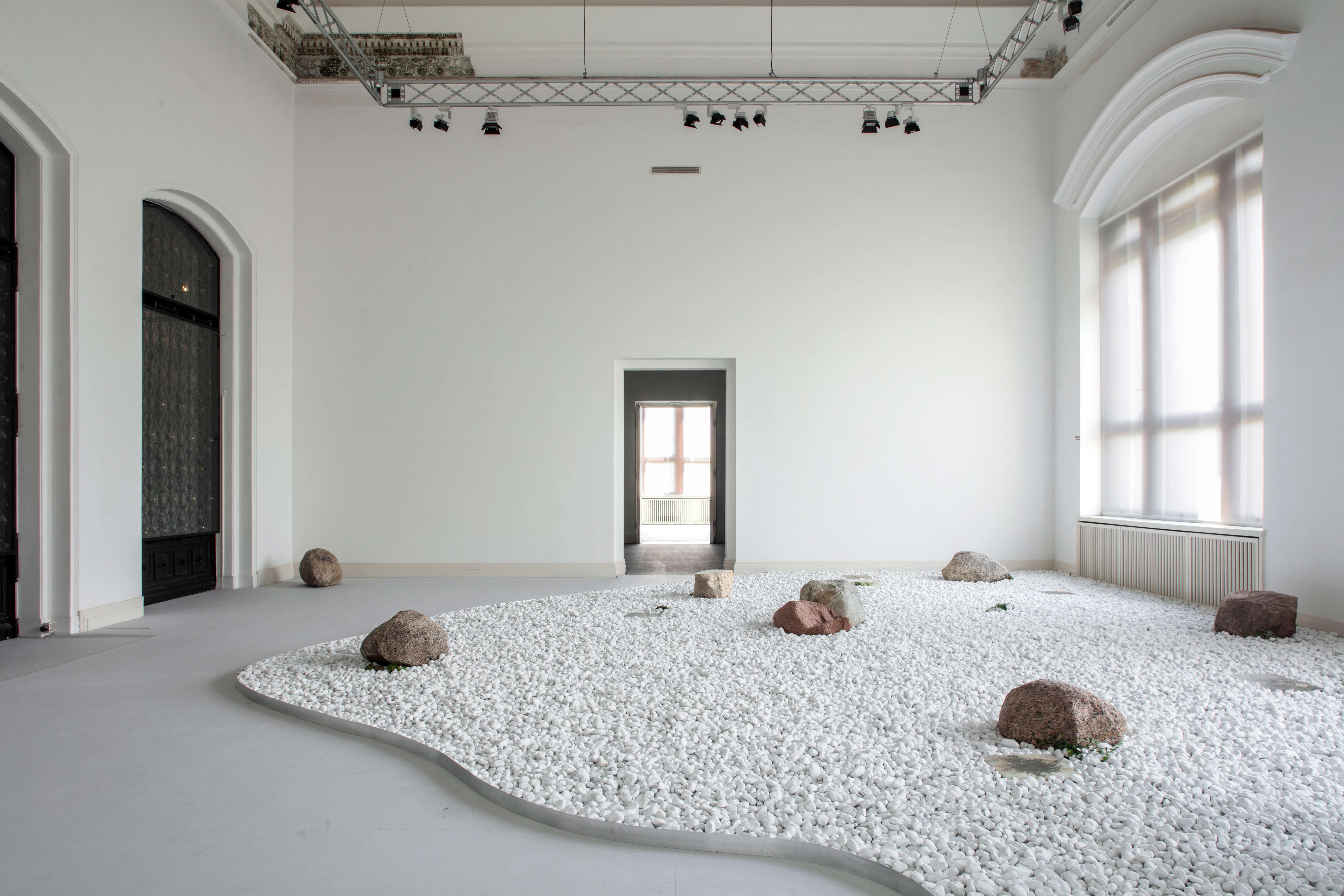 Blick in einen weißen Raum, in dem ein Feld weißer Steine liegen.