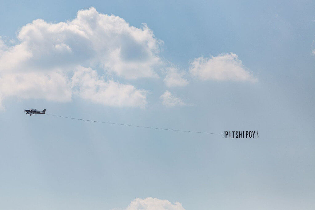 """Das Bild zeigt ein Flugzeug vor einem blauen Himmel, welches ein Banner mit der Aufschrift """"Pitshipoy"""" nach sich zieht."""