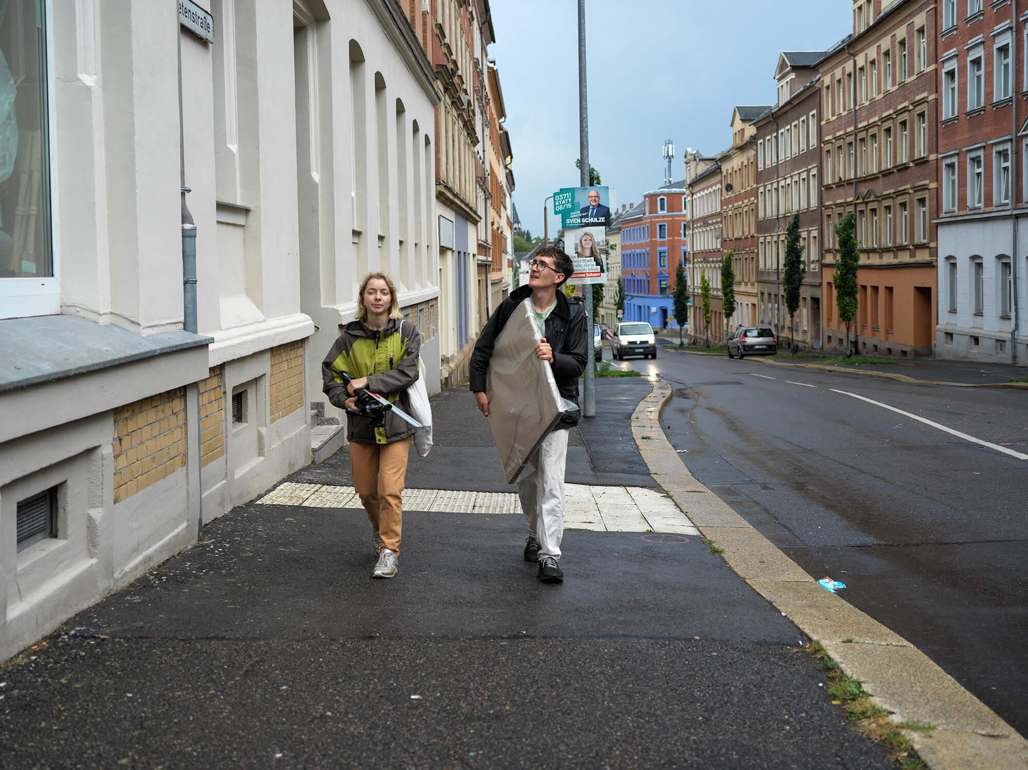 Eine Frau und ein Mann tragen Kunst durch die Straßen von Chemnitz.