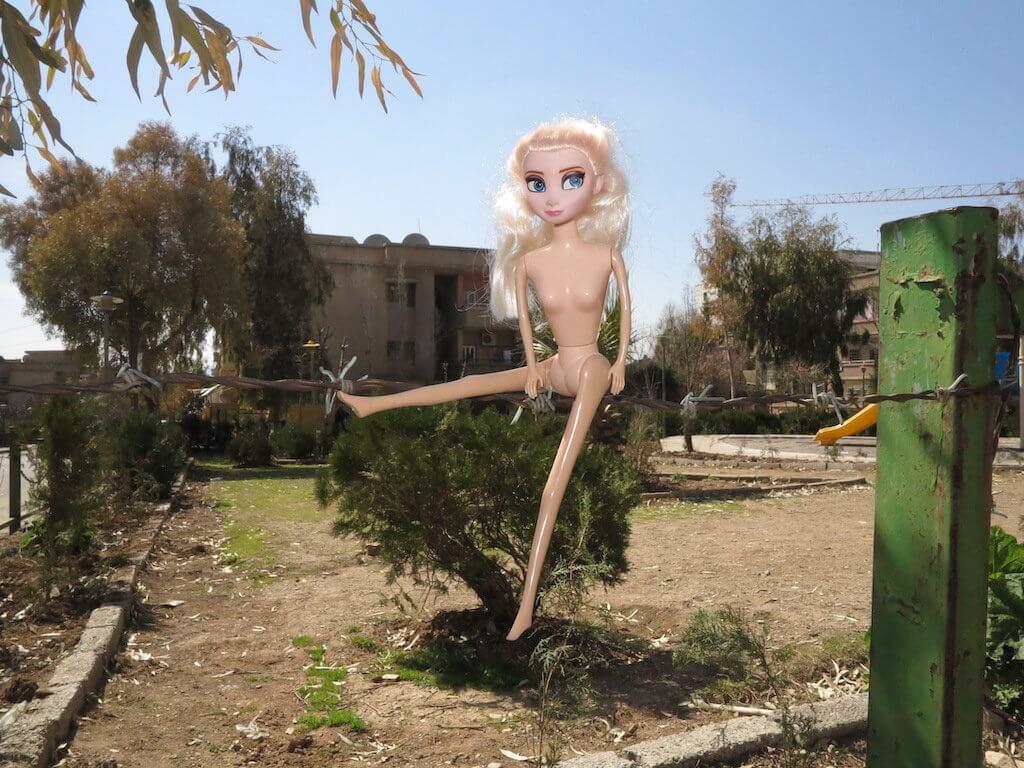 Man sieht eine Barbie Pupe die im Raum vor einer Landschaft schwebt.