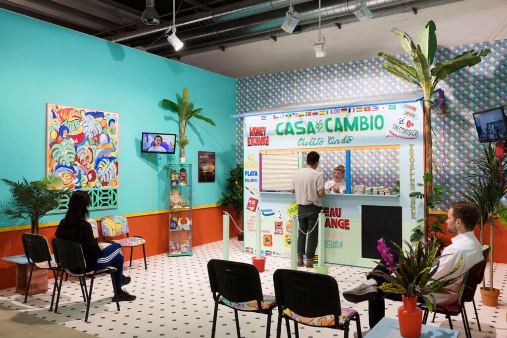 Installation von Sol Calero: Bunter Aufbau im Stile einer Wechselstube vor Raum mit Stühlen und mintfarbenen Wänden.
