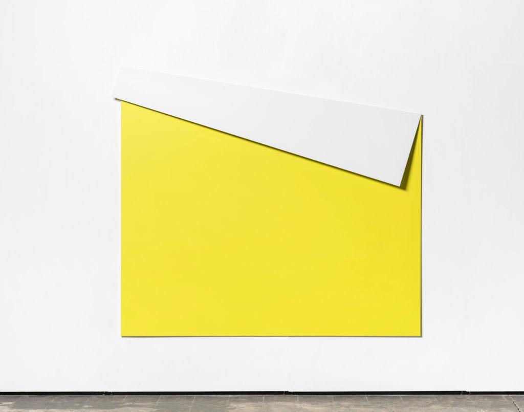 Ansicht eines gelben Bildes vor weißer Wand.