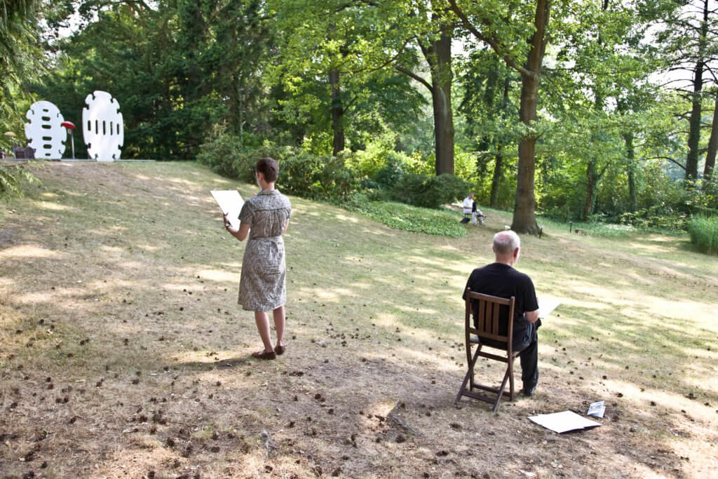 Zwei Personen, die in einem Garten zeichnen.