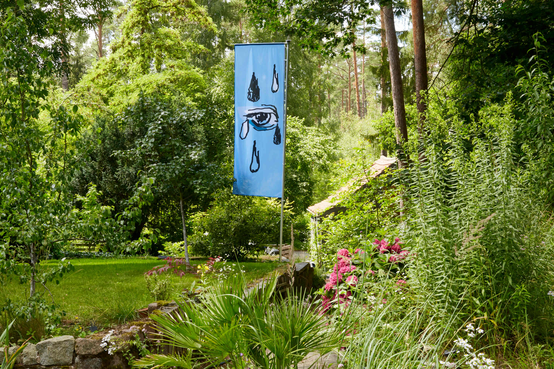 Eine blaue Flagge mit einem Auge und Tränen darauf hängt an einem Fahnenmast im Grünen.