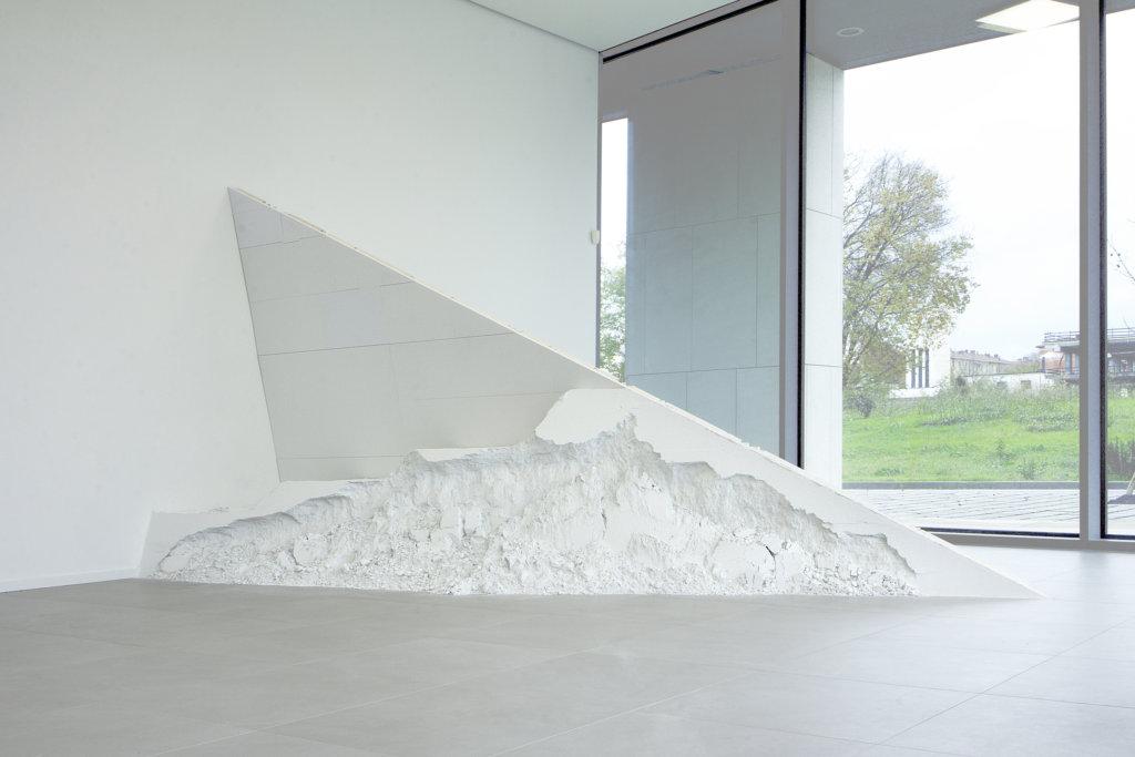 Weißfarbene dreieckige Skulptur vor einem großen Fenster