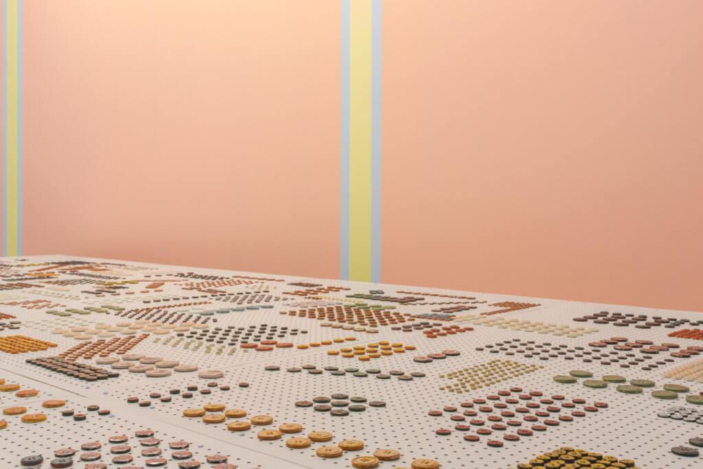 Rosa Wand mit gelben Streifen und davor gemusterter Teppich