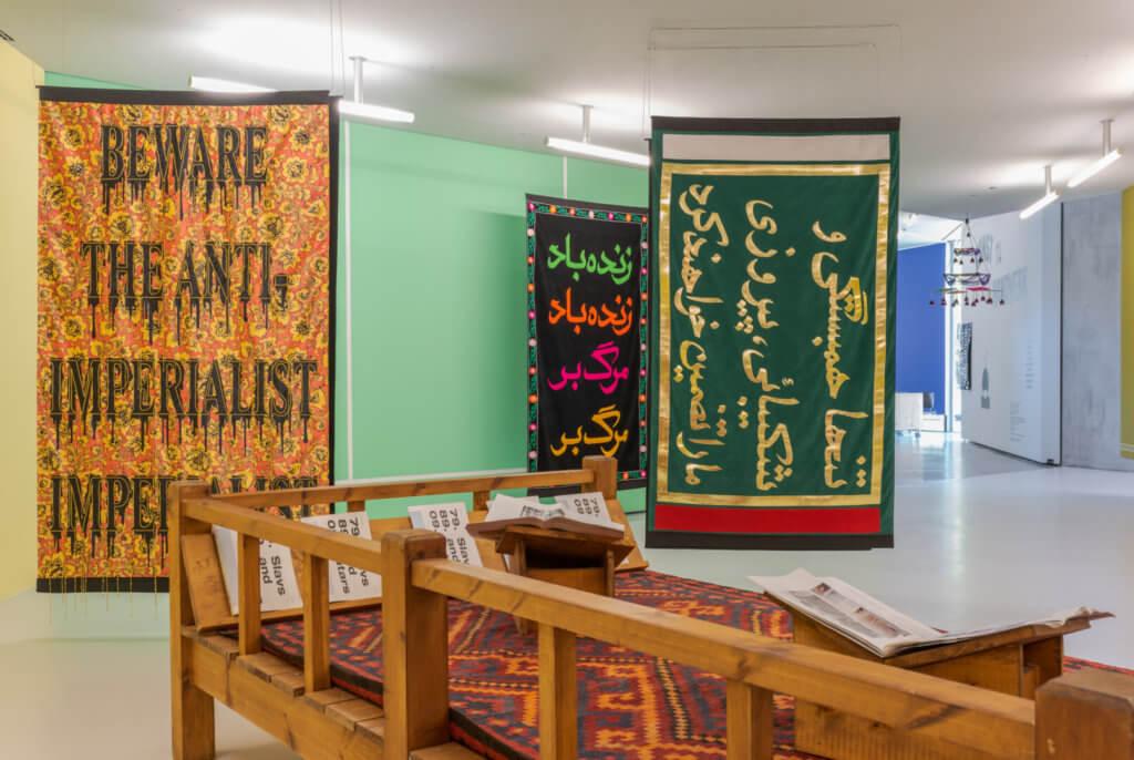 Blick in einen grünen Raum mit Teppichen, auf dem arabische Schriftzeichen sind.