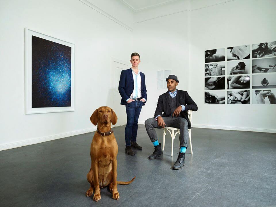 Zwei Männer mit einem Hund in einem weißen Raum.