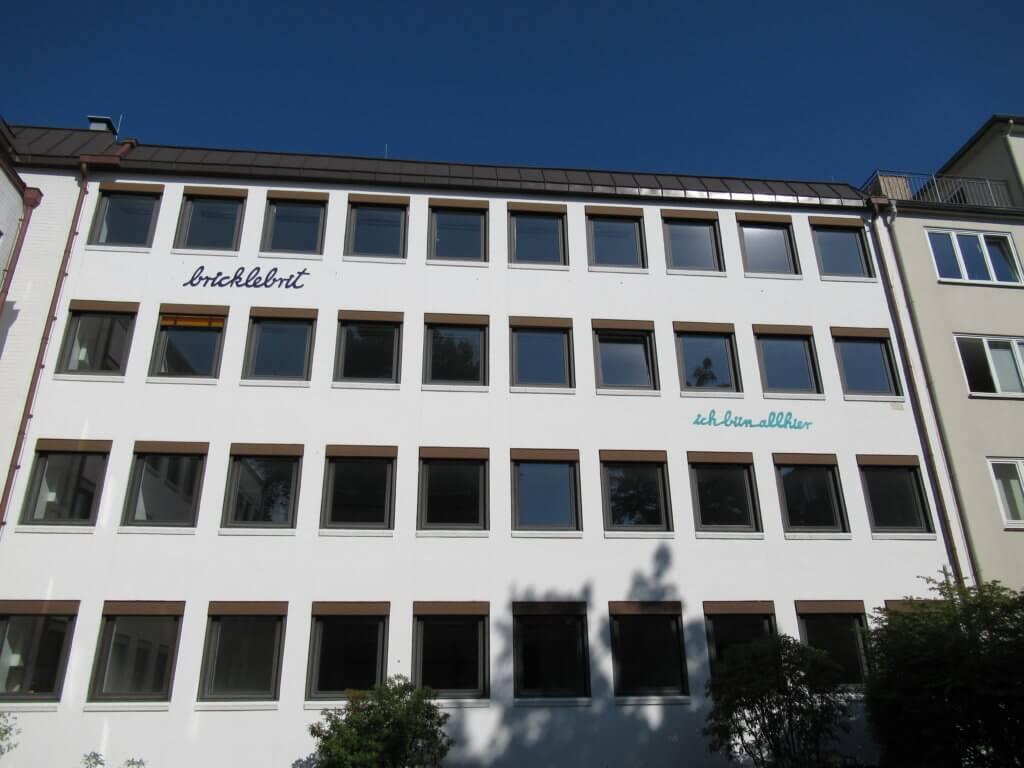 Rupprecht Matthies: bricklebrit & ick bün allhier!, 2020: Schriftzüge in farbiger Schreibschrift an einer Hausfassade