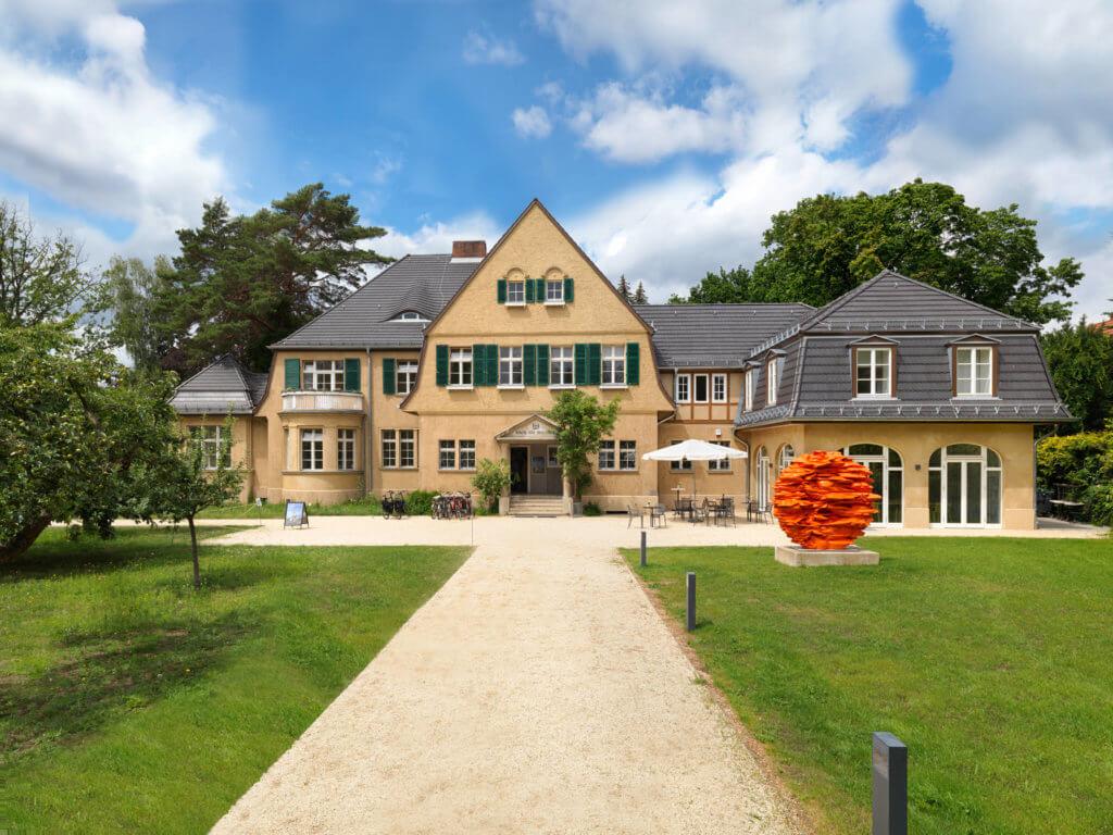 Außenansicht des Haus am Waldsee. Man sieht das Gebäude, die Auffahrt sowie eine orangefarbene Skulptur.