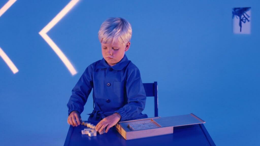 Ein blonder Junge sitzt in einem blauen Zimmer und spielt ein Spiel