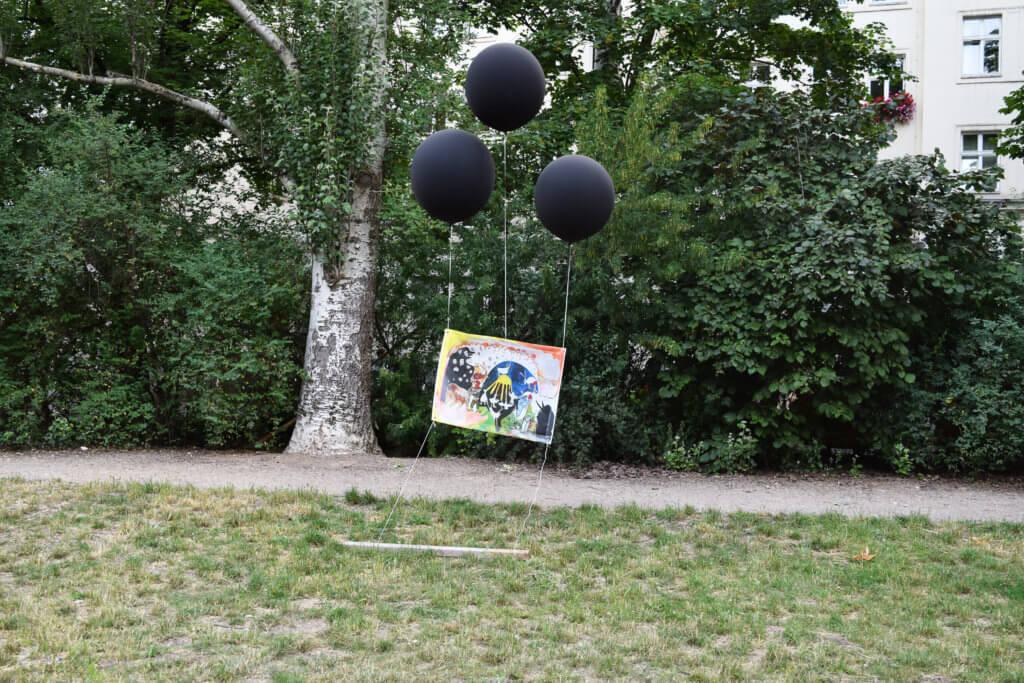 """Ausstellungsansicht """"Ok Park"""" im Berliner Auerpark. Ein Bild wird von drei schwarzen Luftballons in der Luft gehalten. Eine Arbeit von Anne Duk Hee Jordan: """"Lord of the wizard — Last judgement""""."""