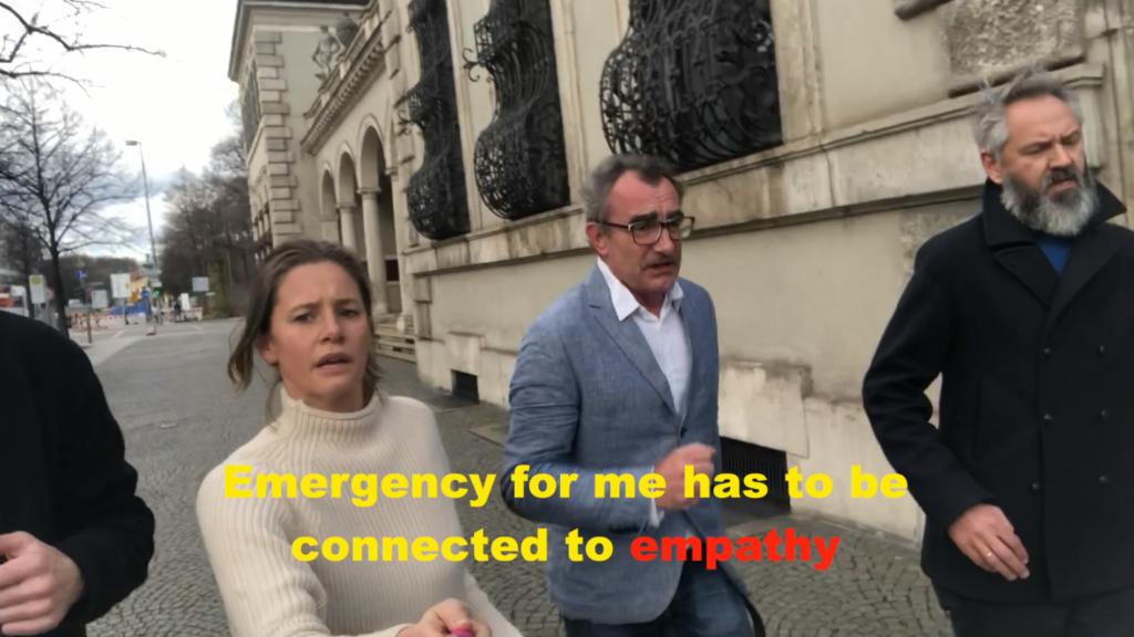 Zu sehen ist ein Videostill der Aktion: Thierry Geoffroy: Critical Run, What is an emergency now - Can we rank Emergencies, abgebildet sind mehrere Menschen, die laufen.