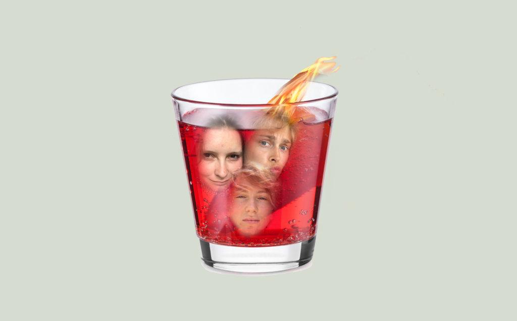 Zu sehen ist ein Aperitiv Glas, gefüllt mit einem roten Drink. In das Gefäß sind 3 Köpfe montiert.