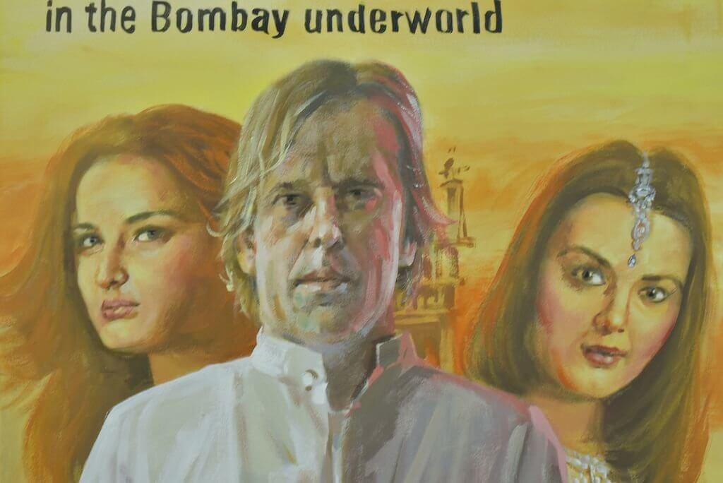 """Zu sehen ist ein Plakat, darauf der Schriftzug """"In the Bombay underworld"""" und drei Personen: ein Mann und zwei Frauen."""