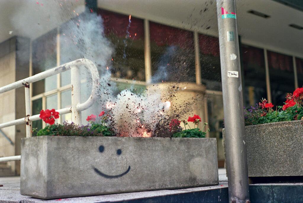 """Zu sehen ist ein Bild aus der  Serie """"Blumensprengungen"""" von Annette Wehrmann. Man sieht einen Blumentopf der explodiert."""