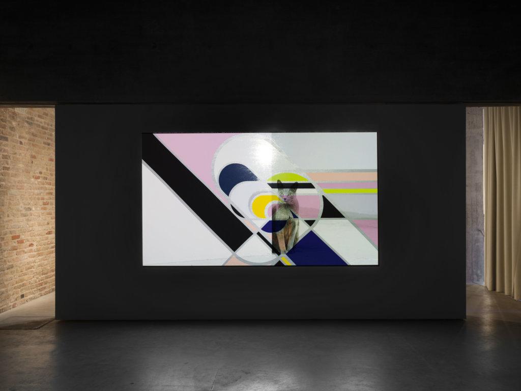 Ausstellungsansicht von Sarah Morris und Alexander Kluge in der König Galerie. Video und Sound. Cats and Ghosts. Auf dem Bildschirm ist eine Katze zu sehen.