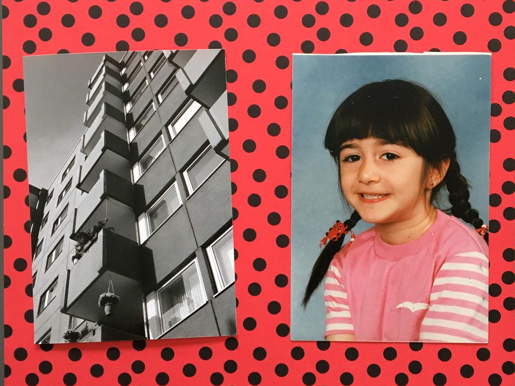 Das Bild zeigt eine Fotocollage bestehend aus drei Teilen. In der linken Seite des Bildes ist eine Schwarz-Weiß Fotografie eines Hochhauses aus Froschperspektive zu sehen. Rechts davon befindet sich die Fotografie eines kleinen Mädchens; sie hat schwarze Haaren, welche zu zwei Zöpfen gebunden sind. Beide Fotografien sind auf einem Roten Untergrund mit schwarzen Punkten angebracht.