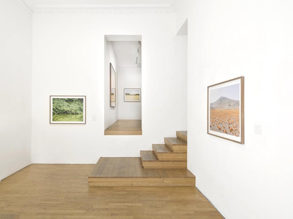 Ausstellungsansicht mit Fotografien von Roger Eberhard in der Robert Morat Galerie Berlin. Weiße Wände und eine Treppe.