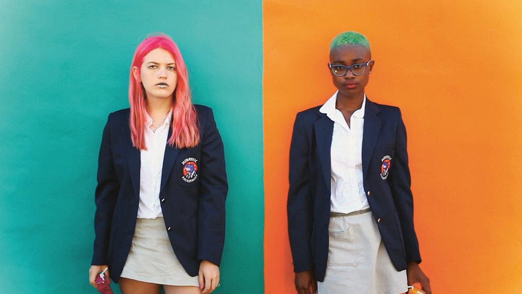 Das Bild zeigt zwei Mädchen vor einer Wand. Die linke Seite der Wand ist in einem starken Türkis gestrichen, die rechte in einem kräftigen Orange. Die Mädchen tragen beide eine Schuluniform, sind jedoch beide aufwendig geschminkt und haben rosa beziehungsweise türkis gefärbte Haare. Das linke Mädchen besitzt weiße, das rechte schwarze Hautfarbe, beide schauen in die Kamera.