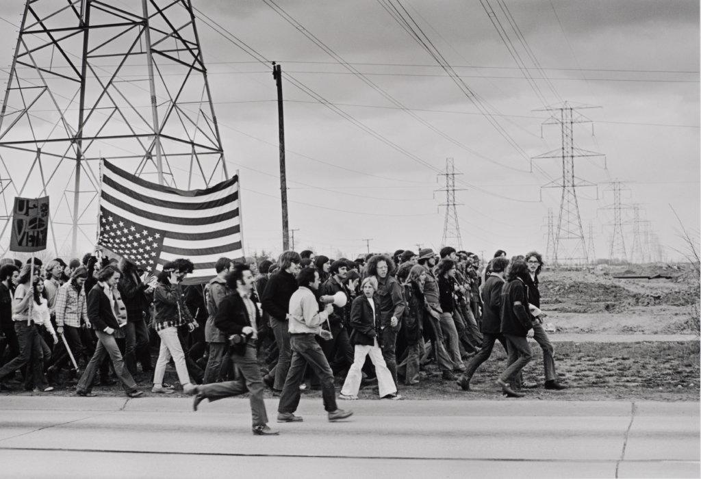 Man sieht eine Menschenmenge in schwarz-weiß von links nach rechts durch das Bild laufen. Es wird eine US-Flagge geschwenkt.