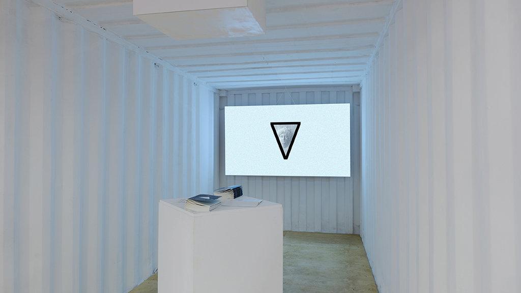 Das Bild zeigt einen länglichen weißen Raum mit Metallwänden. Am hinteren Ende des Raumes ist ein Bildschirm angebracht, auf welchem ein nach unten zeigendes Dreieck zu sehen ist. Etwas vor dem Bildschirm steht ein weißes Podest mit zwei Ordnern oder Büchern darauf.