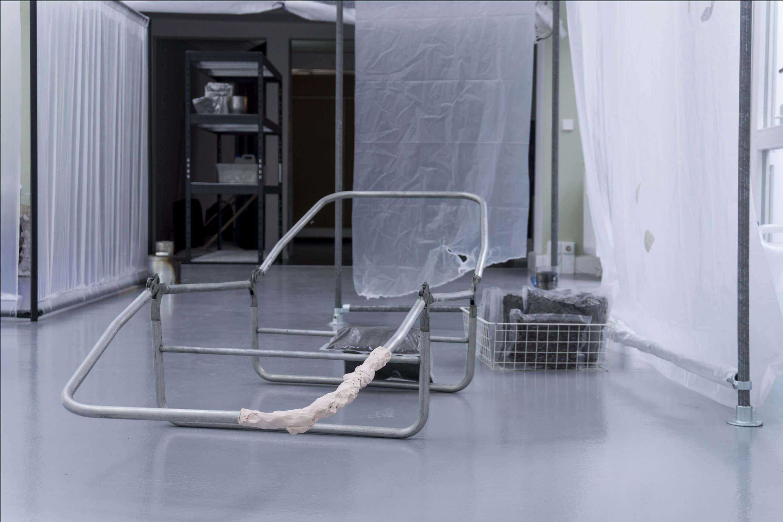 Installationsansicht Alexander Poliček. Verschiede Objekte aus Metall zwischen Plastikplanen.