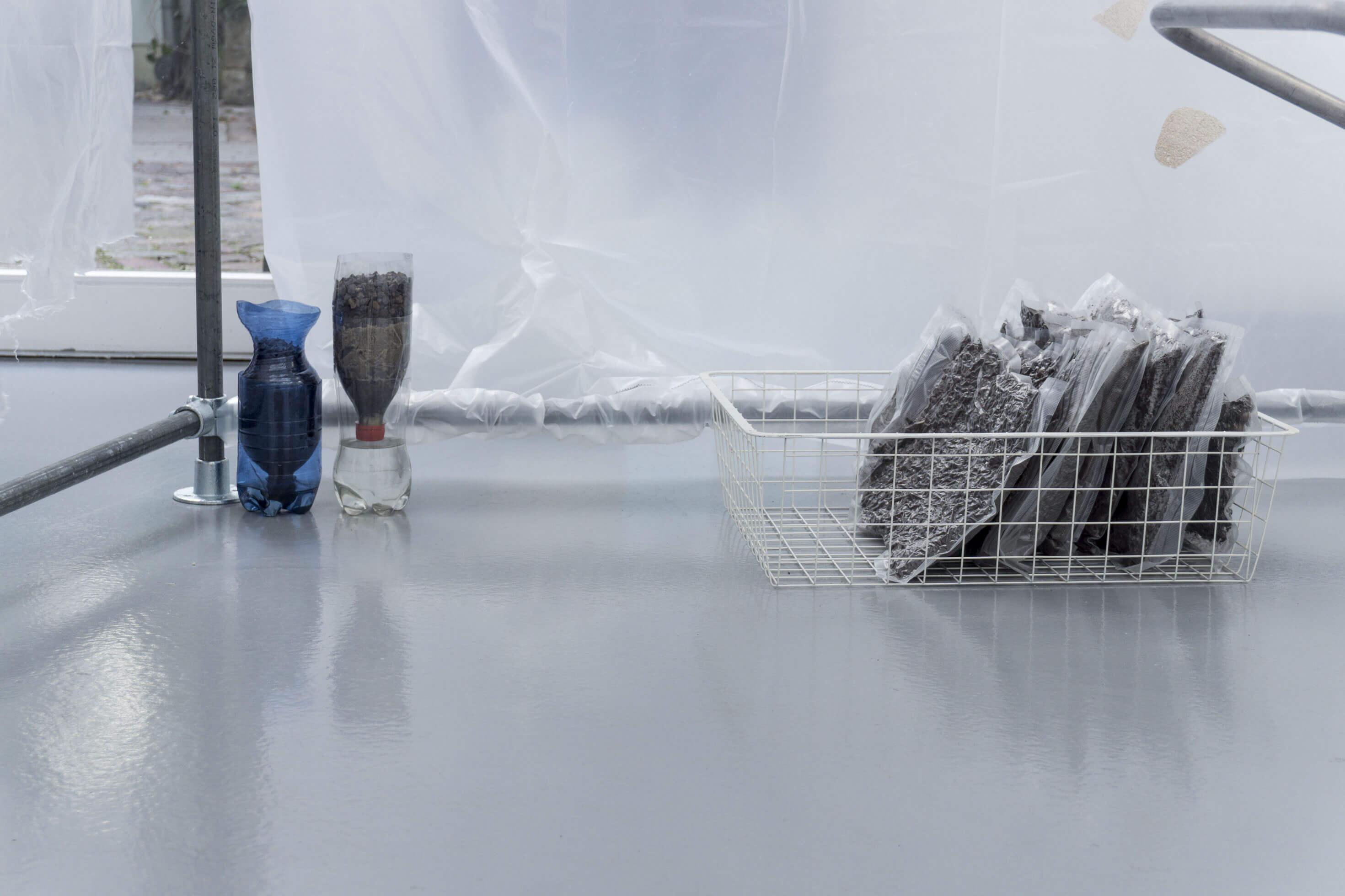 Installationsansicht Alexander Poliček, aufgeschnittene Plastikflaschen und andere Objekte.