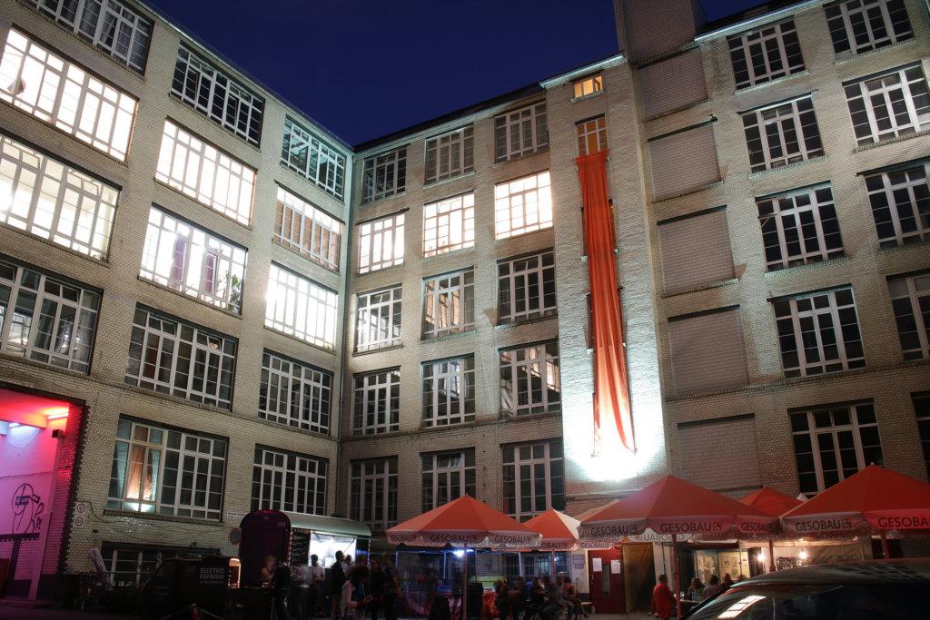 Kunst in den Gerichtshöfen in Berlin Wedding. Beleuchtete Häuserfassade mit herunterhängendem Stoff in Orange. Einige Sonnenschirme.