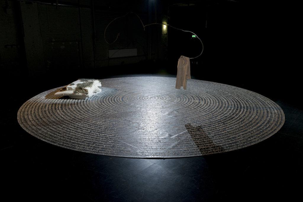Man sieht in weißer Farbe auf den schwarzen Boden des Ausstellungsraum in einer immer enger werdenden Spirale geschriebene Worte.