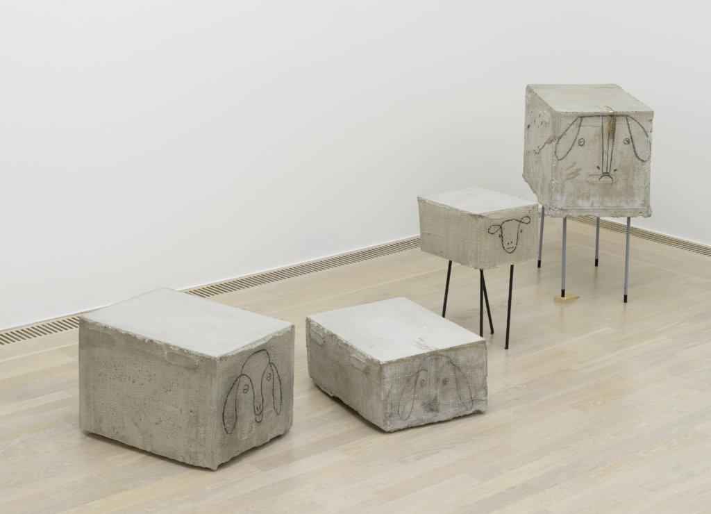 """Zu sehen sind die Arbeiten """"Untitled (Small Sheep 9) / (Small Sheep 2) / (Big Sheep 17) / (Big Sheep 15)"""" von Judith Hopf. Abgebildet sind Betonblöcke, auf die Gesichter von Schafen gezeichnet wurden."""