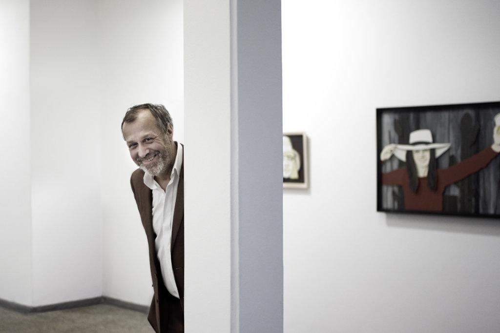 Man sieht den Galeristen Ralf Krüber in seinen Galerieräumen. Er schaut links hinter einer weißen Säule hervor.