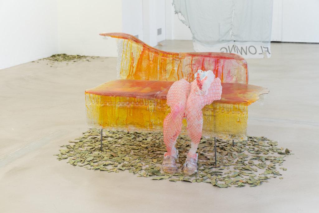 Zu sehen ist die Installation Gory Details von Rebecca Ackroyd. Man sieht eine Skulptur, die wie eine Couch aussieht, darauf sitzend der Abguss zweier Beine.