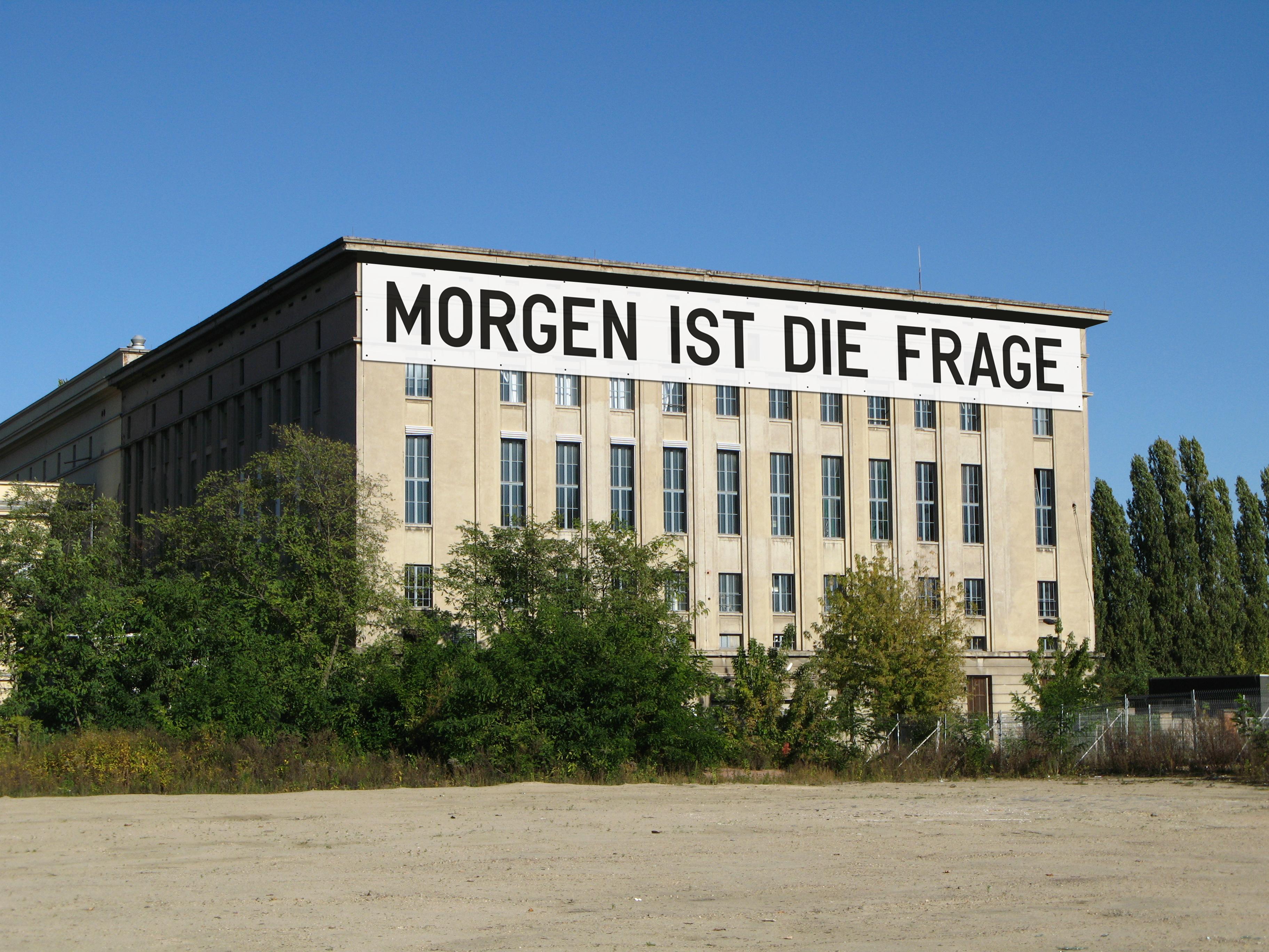Außenansicht der Berliner Clubs Berghain mit einem Banner von Rirkrit Tiravanija, auf dem steht: MORGEN IST DIE FRAGE.