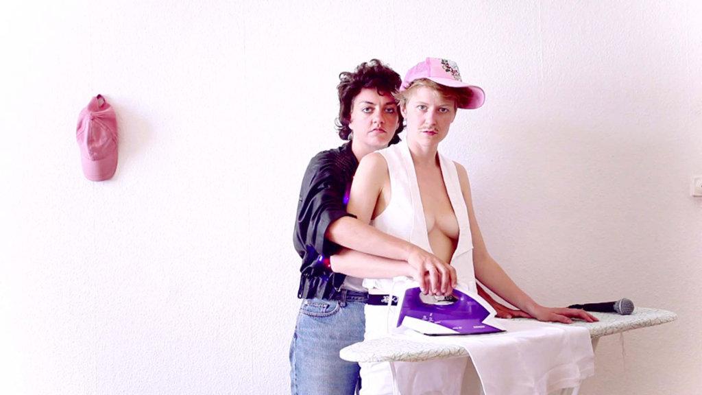 Das Bild zeigt zwei Personen vor einer weißen Wand. Die Personen stehen vor einem Bügelbrett und berühren gemeinsam ein violett-farbebnes Bügeleisen; auf dem Bügelbrett liegt außerdem ein Mikrofon. Beide Personen schauen in die Kamera, es handelt sich um Frauen, welche allerdings als Männer erscheinen und ambivalent gekleidet sind. Das Farbspektrum des Bildes wird durch weiß und rosa bestimmt.